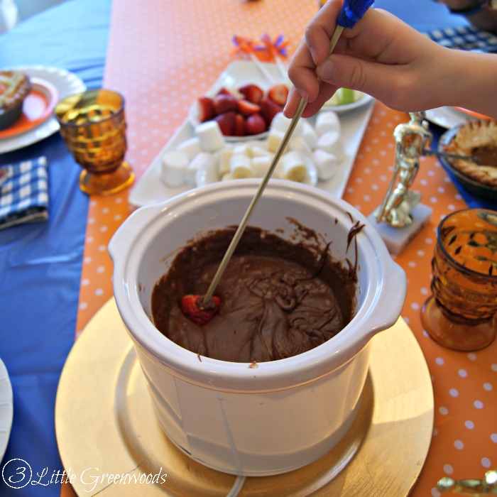 It's a party in a slow cooker! Make this TWO ingredient Chocolate Fondue Recipe for your next celebration! It's the perfect dessert for a Slam Dunk Basketball Party! https://www.3littlegreenwoods.com