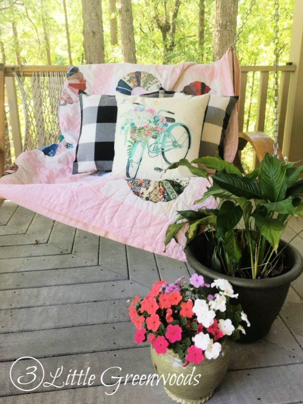 Let's learn how to decorate a front porch for summer! This covered front porch shows how to decorate on a budget with a fantastic summer floral wreath, layered rugs, farmhouse pillow covers, lanterns, and plants. #FrontPorchDecorating #HowToDecorateFrontPorch #SummerFrontPorch